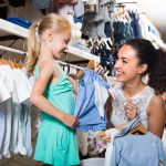 young woman and girl in clothes store