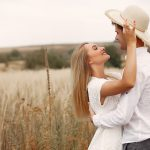 Cute couple in a field. Lady in a white dress. Guy in a white shirt