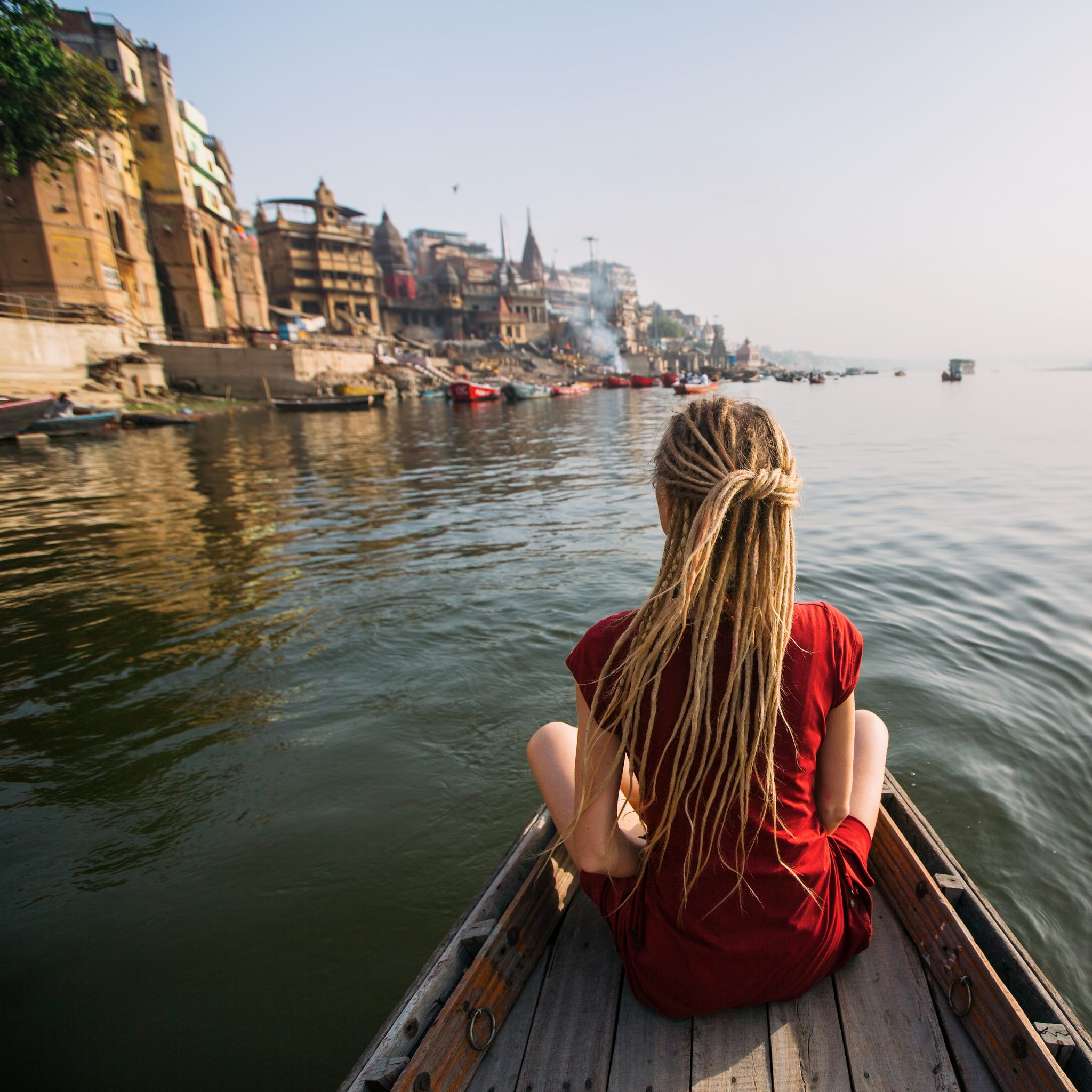 Woman traveler on a boat in the Ganges river waters, Varanasi, India.