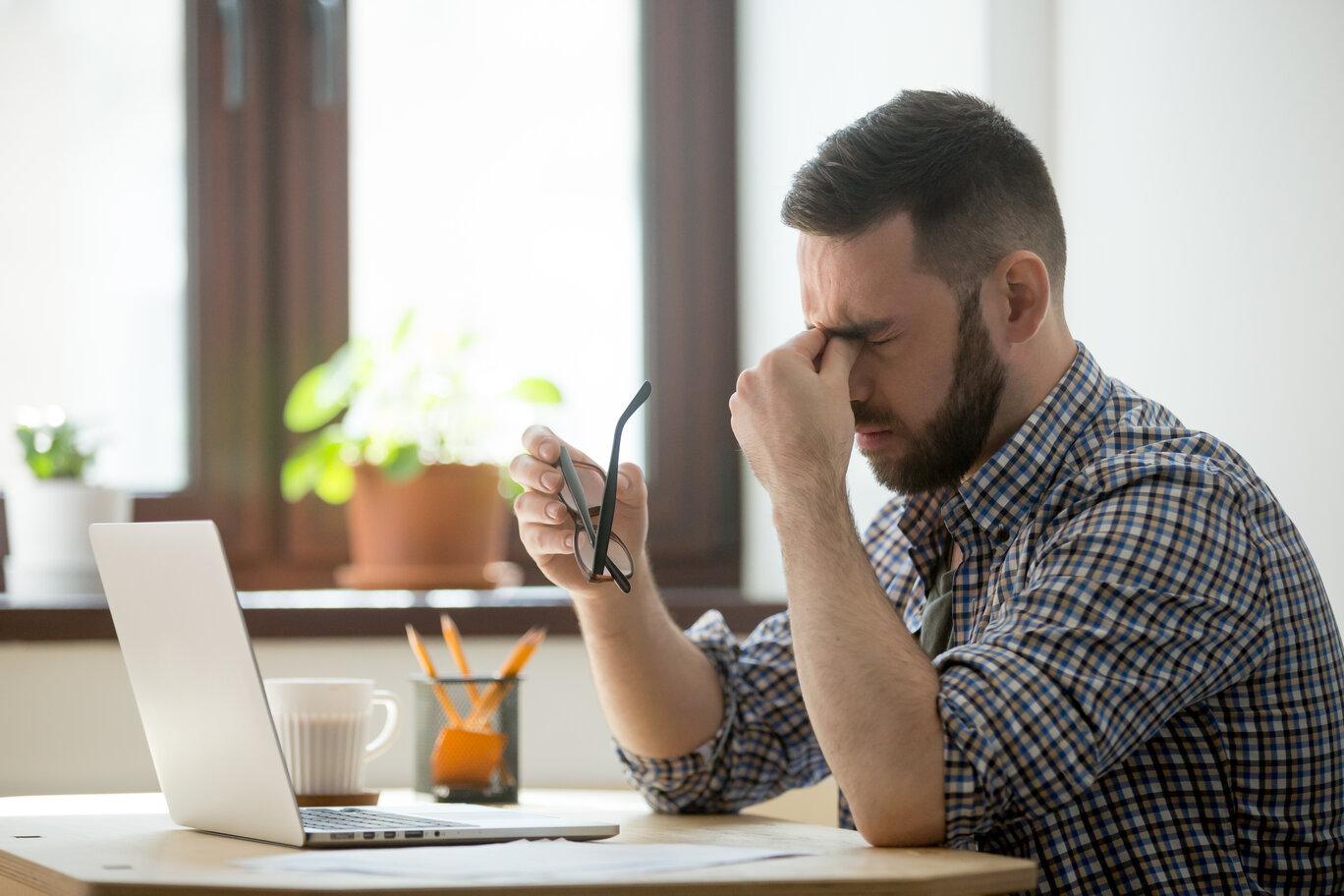 Stressed male massaging nose bridge suffering from headache