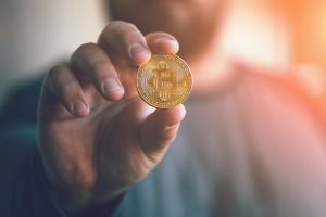 man holding a coin symbolizing cryptocurrency