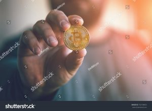 man holding coin symbol of cryptocurrency
