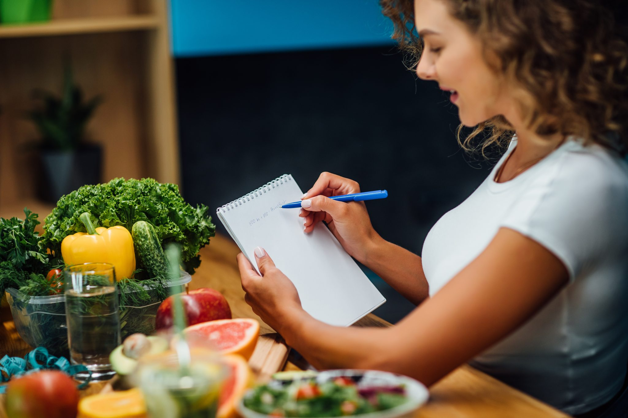 Nutritionist working in office. Doctor writing diet plan on table and using vegetables. Sport trainer.